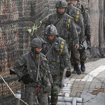 South Korean Army soldiers patrol along a barbed-wire fence near the border village of Panmunjom in Paju, South Korea. (AP)