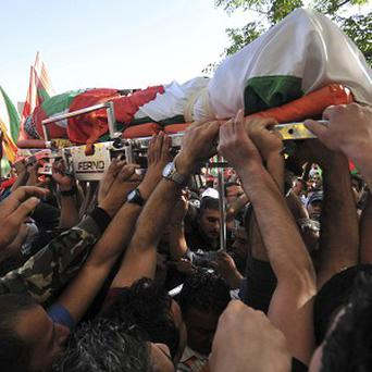 Palestinians carry the body of Maysara Abu Hamdiyeh after it was released by the Israeli authorities (AP)