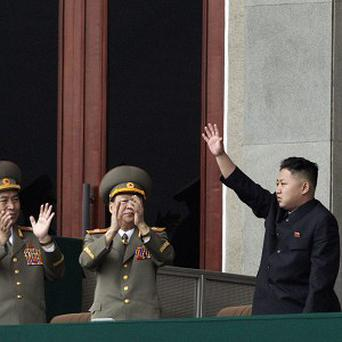North Korean leader Kim Jong Un, left, waves as his military officers clap at a stadium in Pyongyang during a mass meeting (AP)