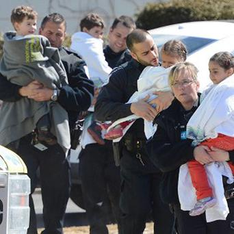 Police carry children from a safehouse to waiting parents and guardians after a shooting at a day care in Gatineau, Quebec (AP)