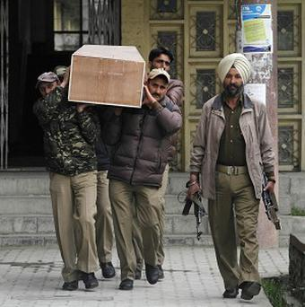 Indian police carry a coffin containing the body of a female British tourist after conducting medical examination in Srinagar, India (AP/Mukhtar Khan)