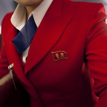 A North Korean Air Koryo attendant wears a pin showing portraits of the late North Korean leaders Kim Il Sung and Kim Jong Il (AP)