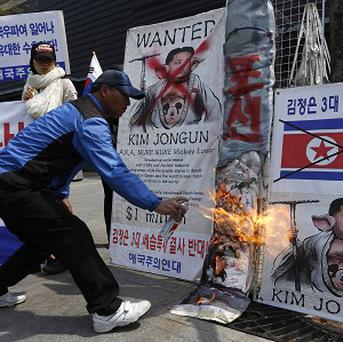 A South Korean protester burns banners with pictures of North Korean leader Kim Jong Un during an anti-North Korea protest in Seoul (AP)