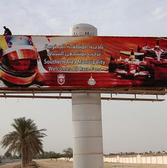 Workers secure a billboard welcoming Formula One fans in English and Arabic along a highway near the Bahrain International Circuit (AP)