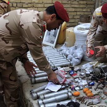 Soldiers inspect explosives seized during recent operations in Baghdad's Adhamiya district (AP Photo)