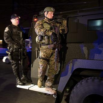 Heavily armed officers join the hunt for the suspect in Watertown (AP)