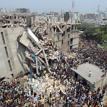 People and rescuers gather after an eight-storey building housing several garment factories collapsed near Dhaka, Bangladesh (AP Photo)