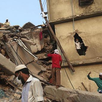 Bangladeshi rescue workers search the rubble at the site of a building that collapsed Wednesday in Savar, near Dhaka (AP)