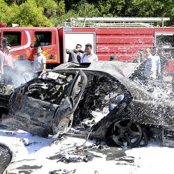 Firefighters extinguishing burning cars after a bomb exploded in Damascus (AP)
