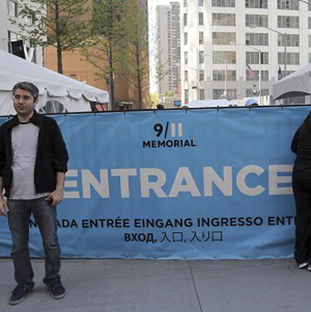 A visitor to the September 11 Memorial poses for a photo as others peer at the entrance line (AP)