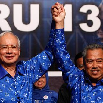 Malaysian prime minister Najib Razak, and his deputy Muhyiddin Yassin celebrate after winning the national generations (AP)