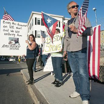 Protesters hold signs outside a funeral home attacking the proposal by family to bury Boston marathon bombing suspect Tamerlan Tsarnaev in the United States (AP)