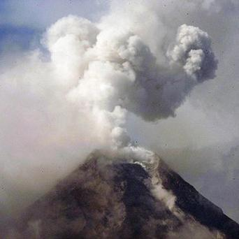 A column of ash shoots up to the sky in a mild eruption of the Mayon volcano (AP/Bullit Marquez)
