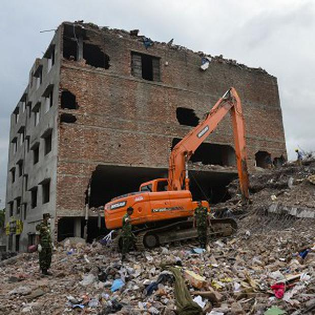 Workers and army personnel use heavy machinery as they work to clear the site of the collapsed factory in Bangladesh (AP)