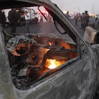 A destroyed car smolders after the tanker truck exploded (AP)