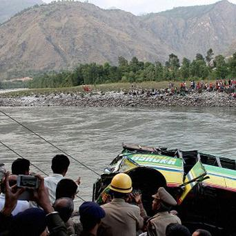 Rescuers look at a bus that plunged into the Beas River near Kullu, India (AP)