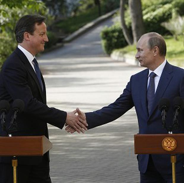 Russian president Vladimir Putin shakes hands with David Cameron after their meeting in the Bocharov Ruchei residence in Sochi (AP)