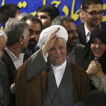 Former president Akbar Hashemi Rafsanjani waves to reporters as he registers his candidacy for the upcoming presidential election at the election headquarters of the interior ministry in Tehran, Iran (AP)