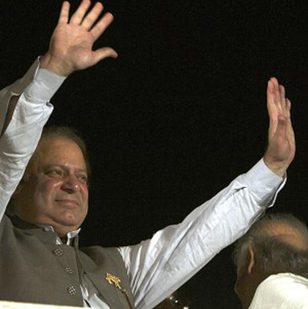Nawaz Sharif waves to his supporters at a party office in Lahore, Pakistan (AP/KM Chaudary)