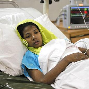 Seamstress Reshma Begum receives treatment at a hospital in Savar, near Dhaka, Bangladesh, after being rescued from a collpased garment factory after 17 days (AP)