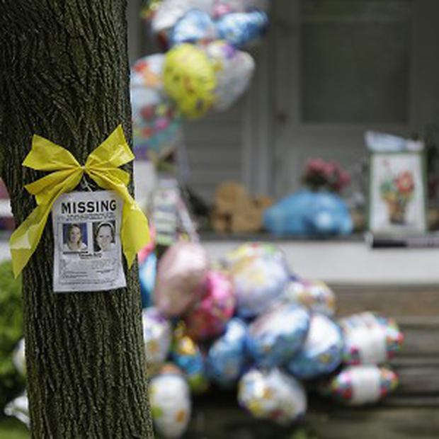 A missing poster still hangs on a tree at the home where Amanda Berry is staying in Cleveland (AP)