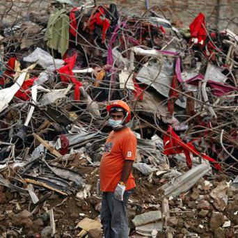 A Bangladeshi rescuer stands amid the rubble of a garment factory building that collapsed on April 24 (AP/AM Ahad)