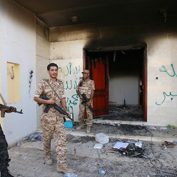 Guards check the burned out US consulate in Benghazi after last year's attack (AP)