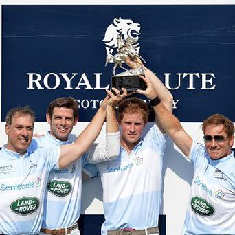 Michael Carrazza, Malcolm Borwick, Prince Harry and Marc Ganzi lift the winners trophy