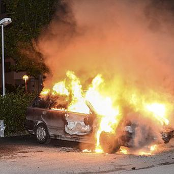 A car is set on fire during the riots