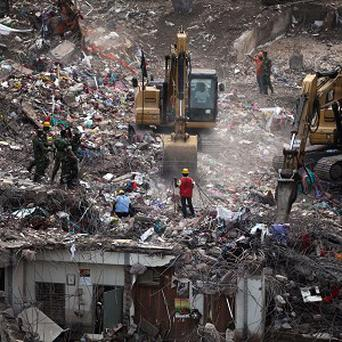 Bangladeshi rescuers use heavy machinery to clear rubble of a clothing factory building that collapsed in Bangladesh (AP/AM Ahad)
