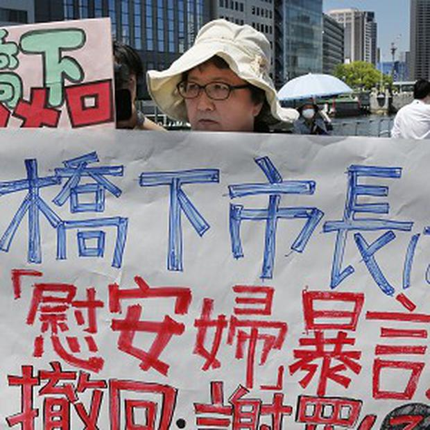 A protester holds a banner at a rally against Osaka mayor Toru Hashimoro in a row over wartime sex slaves (AP)