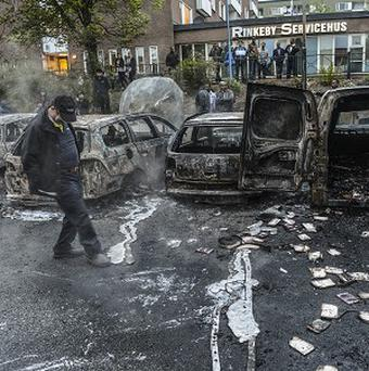 A resident examines burnt cars in the Stockholm suburb of Rinkeby after youths rioted in several different suburbs for a fourth night (AP)