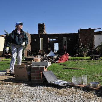 Bobbie Steenbergen walks outside of what is left of her home that was destroyed by the tornado that swept through central Oklahoma on Friday afternoon (AP)