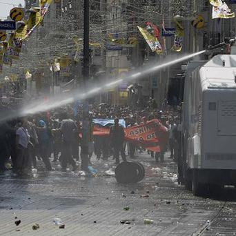 Riot police clash with demonstrators after they used tear gas and pressurised water in a dawn raid to rout a peaceful demonstration (AP)