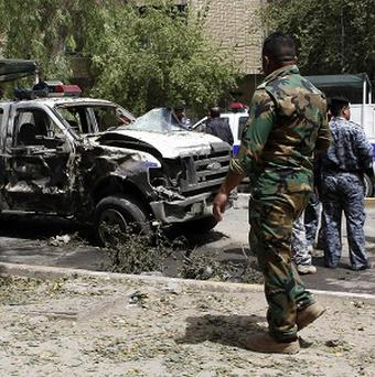 Security forces inspect the scene of a car bomb attack in the commercial area of Karradah in Baghdad, Iraq, on Thursday (AP)