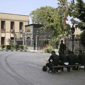 Egyptian anti-riot soldiers sit outside of the Shura Concil, in Cairo (AP)