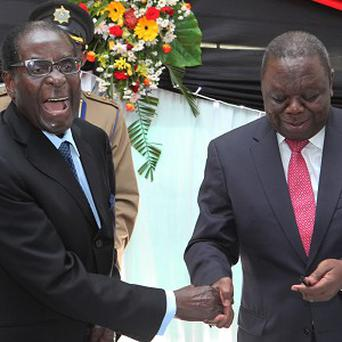 Zimbabwean president Robert Mugabe, left, has announced elections will be held this summer despite the objections of prime minister Morgan Tsvangirai, right (AP)