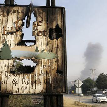 The sign for the Lake Elizabeth Golf and Ranch Club stands in the foreground as smoke looms up in the distance (AP)