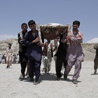 Men carry the bodies of seven civilians killed by a roadside bomb in the Alingar district of Laghman province in Afghanistan (AP)
