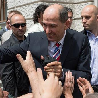 Sovenia's former prime minister Janez Jansa greets supporters as he exits a court building (AP)
