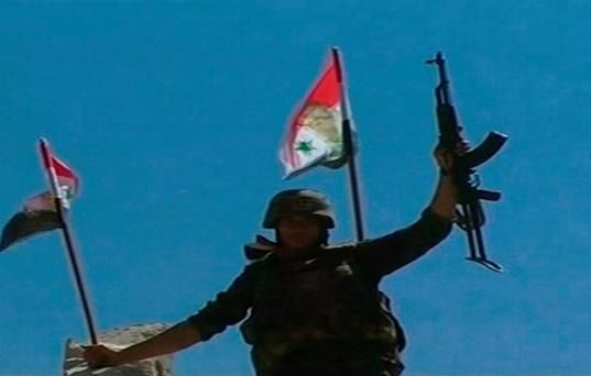 A soldier raises his weapon while holding a Syrian flag in Qusair after the Syrian army took control of the city from rebel fighters