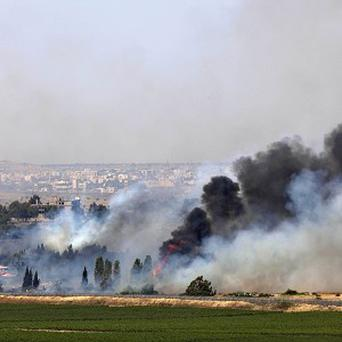 Smoke rises as Syrian government troops battle rebels near the village of Quneitra near the border with Israel. (AP)