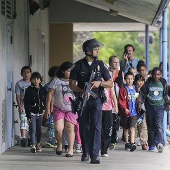 A police officer leads children on a field trip out of Santa Monica College (AP/Reed Saxon)