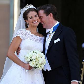 Princess Madeleine of Sweden and Christopher O'Neill smile at wellwishers following their marriage ceremony in Stockholm
