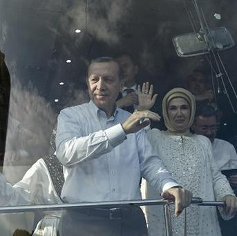Turkish Prime Minister Recep Tayyip Erdogan and his wife Emine wave to supporters after his arrival in Ankara, Turkey (AP)