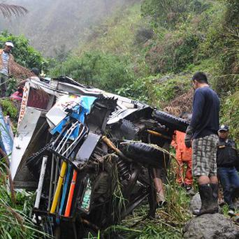 Police officers inspect the wreckage of a van that veered off a mountain road in the remote Buguias town in Benguet province (AP)