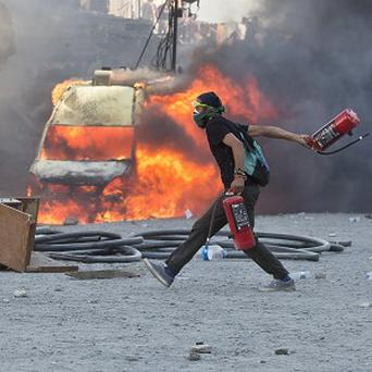 A man runs carrying fire extinguishers past a burning van during clashes at Taksim Square in Istanbul (AP)
