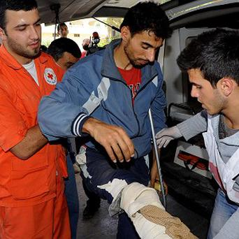 Members of the Lebanese Red Cross help a Syrian man who was wounded in Qusair, Syria, during battles between rebels and government forces (AP)