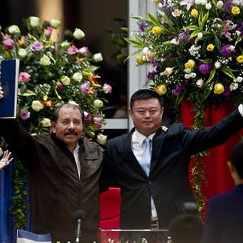 Nicaragua's President Daniel Ortega and Chinese businessman Wang Jing hail a deal to build a canal across the country (AP)