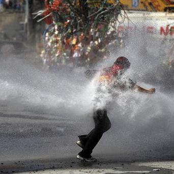A protester is hit by police water cannon in Taksim square in Istanbul (AP)
